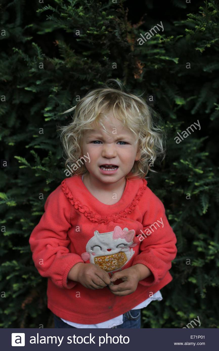 A two year old girl making an angry face. - Stock Image