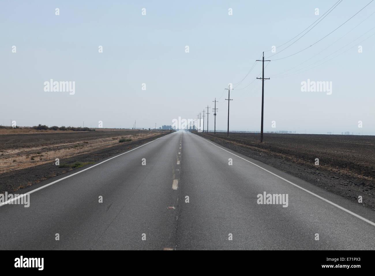 Rural highway fading into the horizon in San Joaquin Valley farmland - California USA - Stock Image