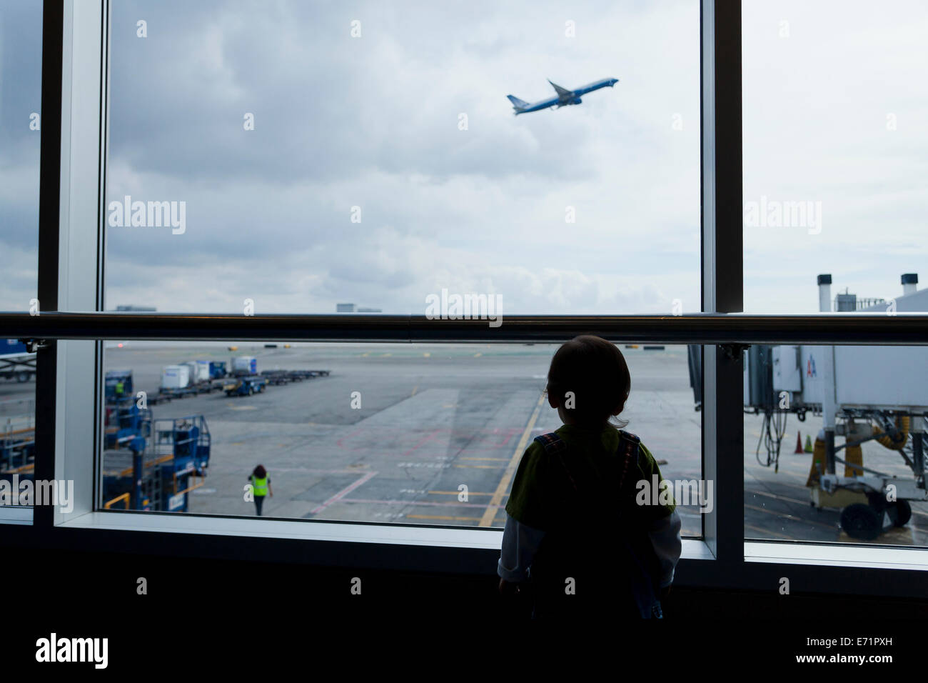 Small child watching departing airliner through airport window - USA - Stock Image
