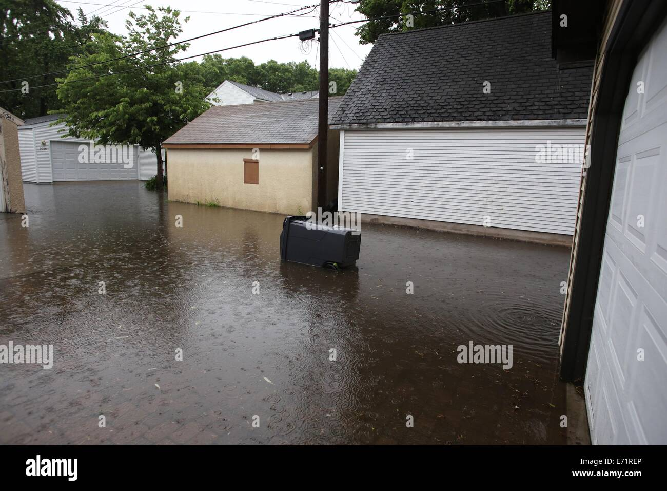 An overturned garbage bin in a flooded alley in Minneapolis, Minnesota. - Stock Image