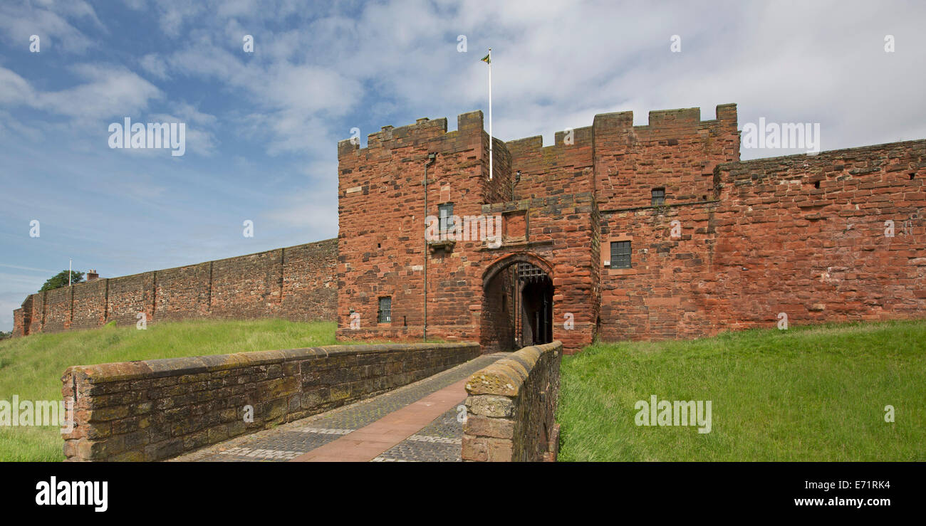 Historic Carlisle castle with imposing red sandstone walls and entrance with portcullis, surrounded by grassy moat - Stock Image