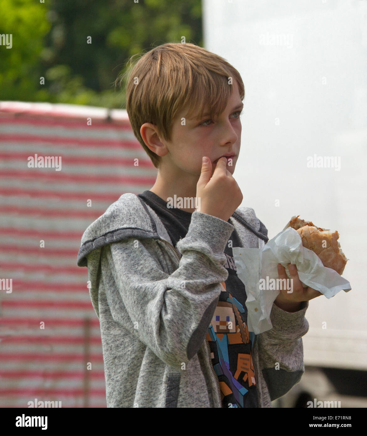 Young boy wearing casual clothes eating hamburger wrapped in paper and licking fingers - Stock Image