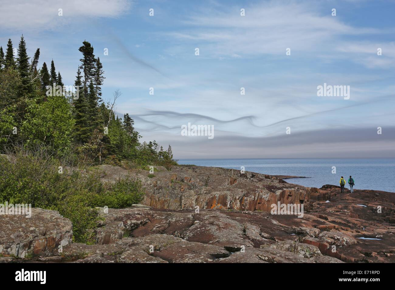 Two people hiking beneath beautiful, wispy clouds on the rocky shore of Lake Superior. - Stock Image