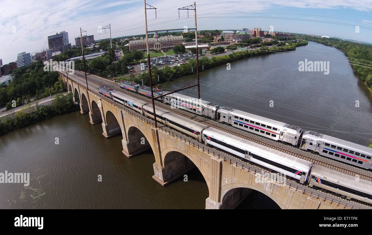 Aerial image of trains crossing the Northeast Corridor Railroad Bridge over the Raritan River in New Brunswick, - Stock Image