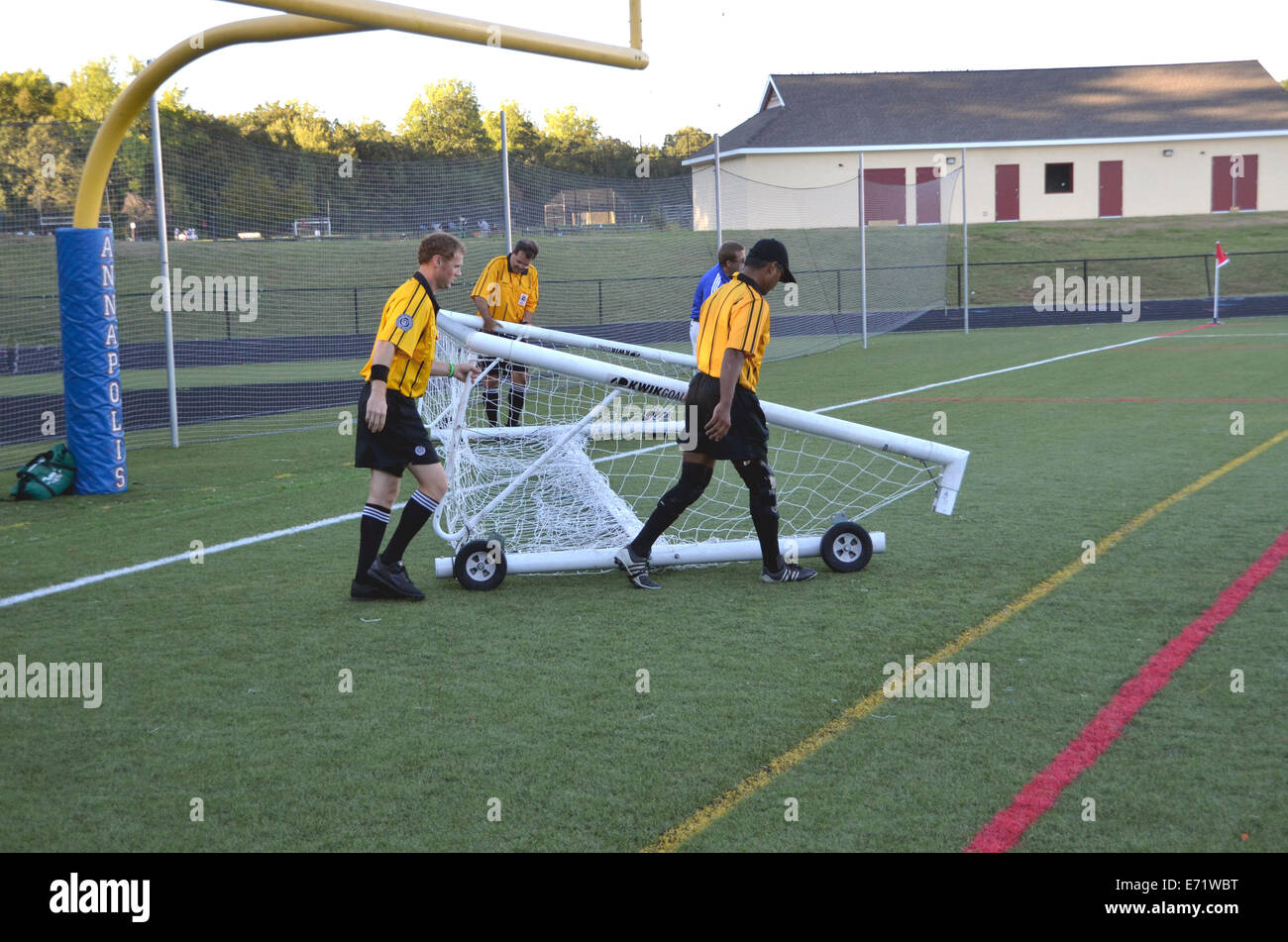 Soccer referees remove a broken goal netting at a high school soccer game - Stock Image