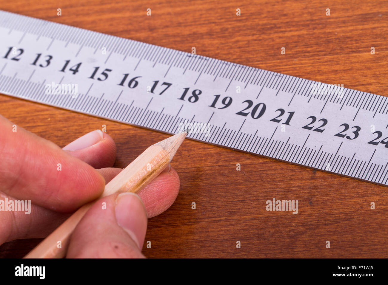 Macro view of hand holding wood pencil and steel ruler for engineering drawing on wooden table. - Stock Image