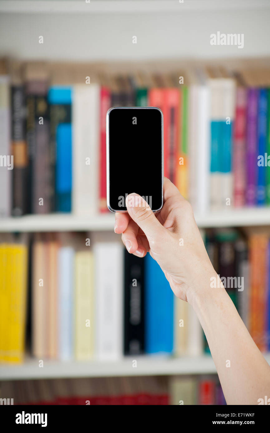 blank screen smartphone in woman hands at library - Stock Image