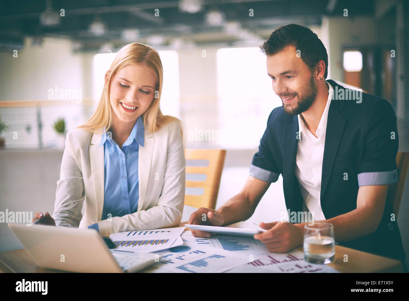 Friendly managers analyzing electronic information at meeting - Stock Image