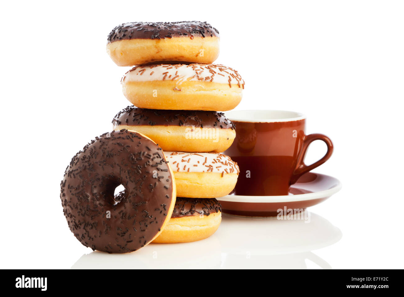 Stacked dark and white chocolate sprinkle donuts and coffee cup isolated on white background - Stock Image