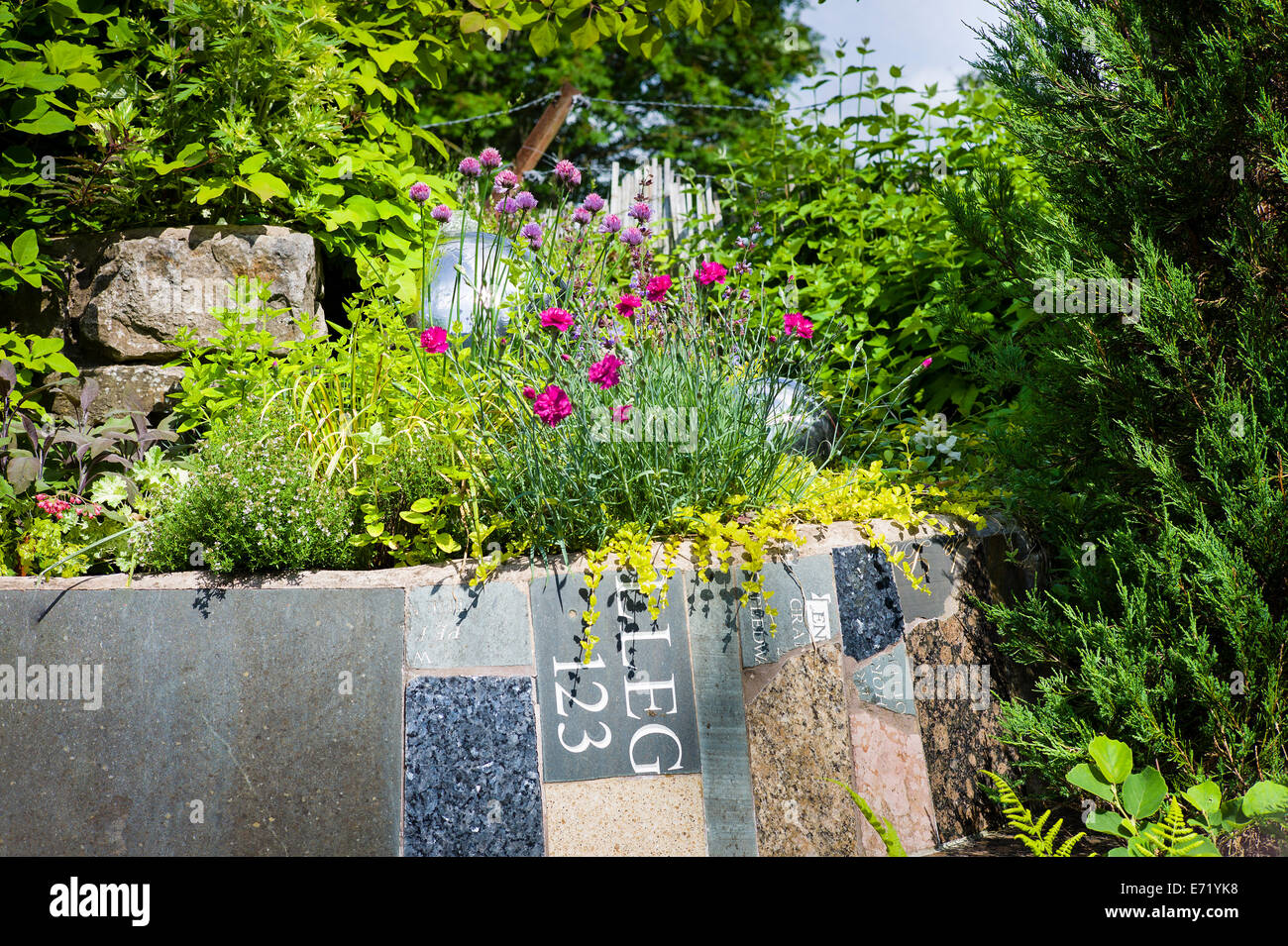 Small secition of an educational garden made from collected scrap pieces by Council services - Stock Image