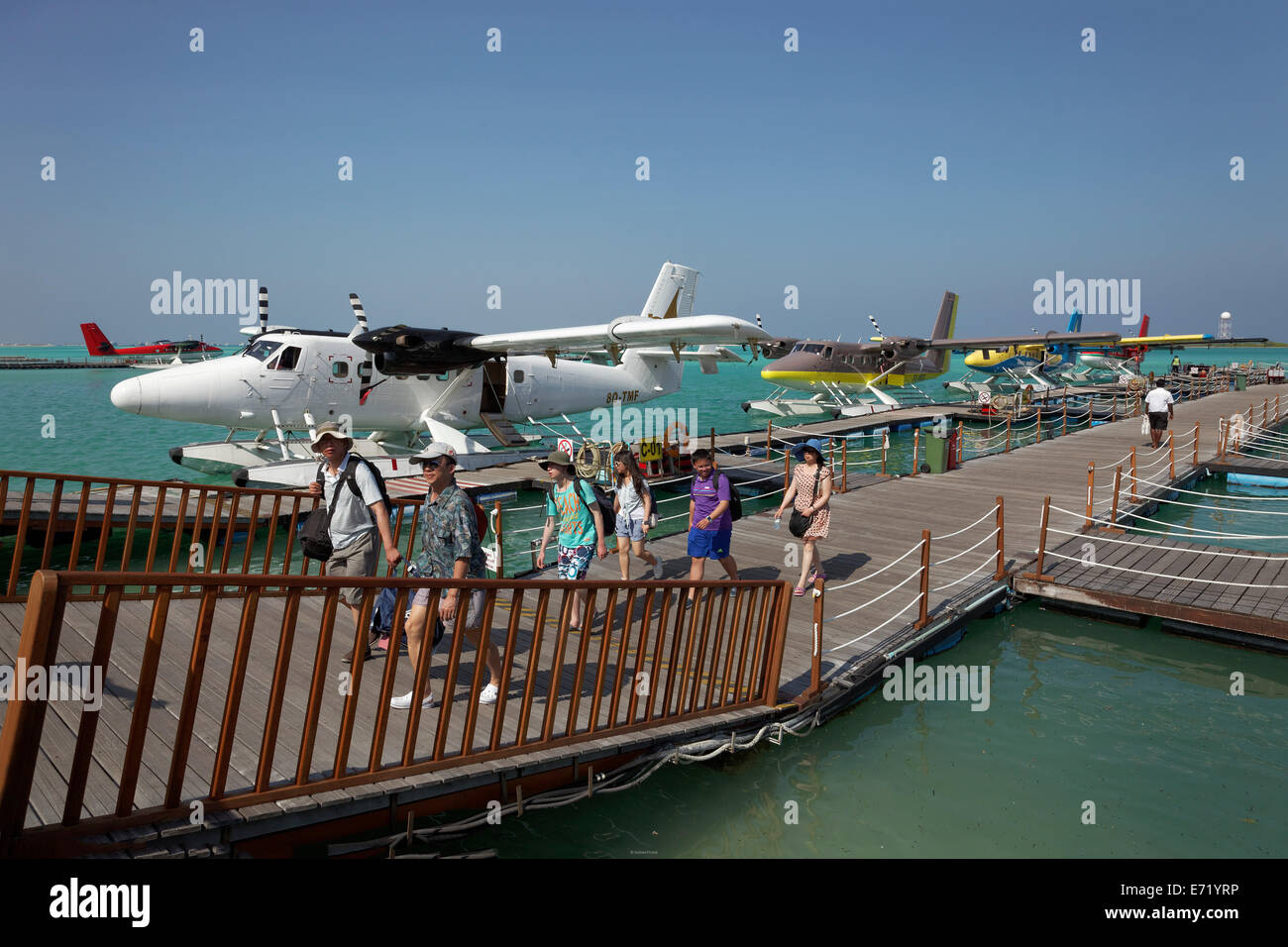 Tourists leaving the pontoon with hydroplanes moored, De Havilland Canada DHC-6 300 Twin Otter, Malé International - Stock Image