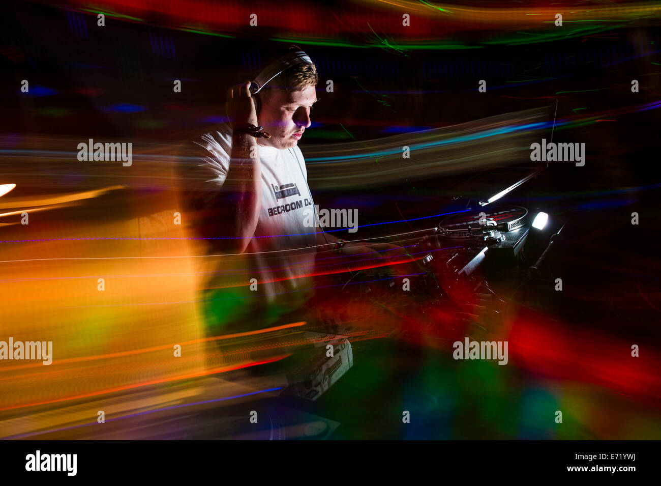 A man DJ'ing at a dance music disco party rave event UK - light trails long exposure  camera movement - Stock Image