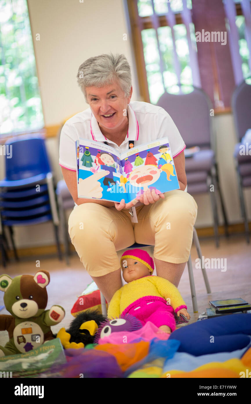 A woman leading a pre-school playgroup, reading a story from a welsh language book,  Wales UK - Stock Image