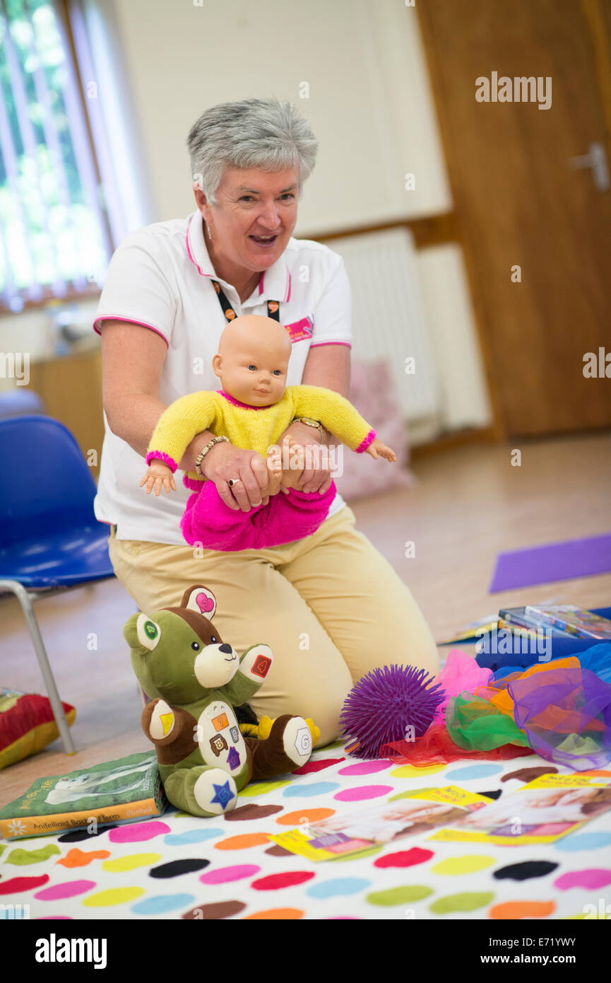 A woman leading a pre-school playgroup showing how to hold a baby for a massage , Wales UK - Stock Image