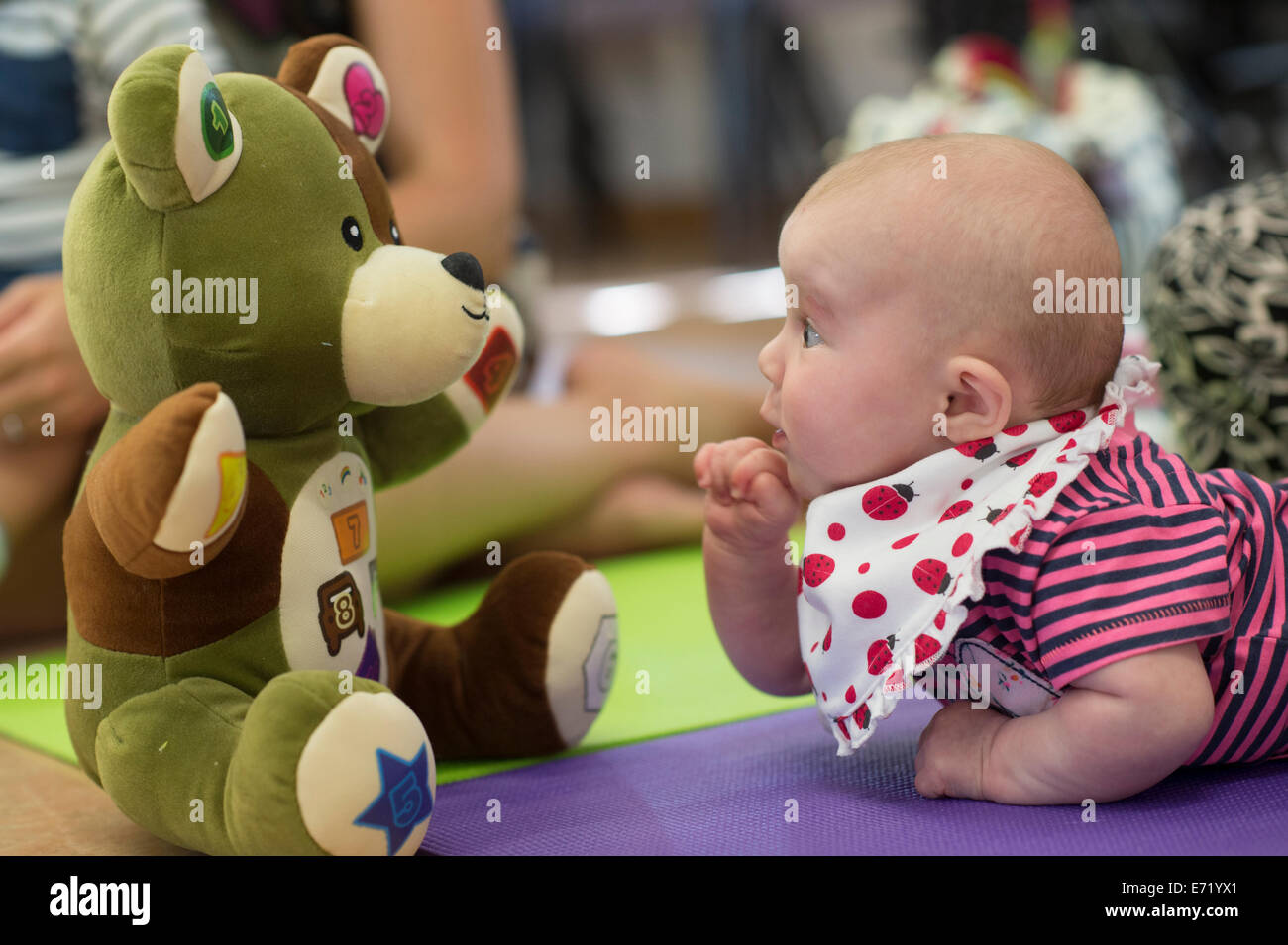 A surprised looking baby boy encountering a big soft toy teddy bear at a pre-school playgroup nursery, Wales UK - Stock Image