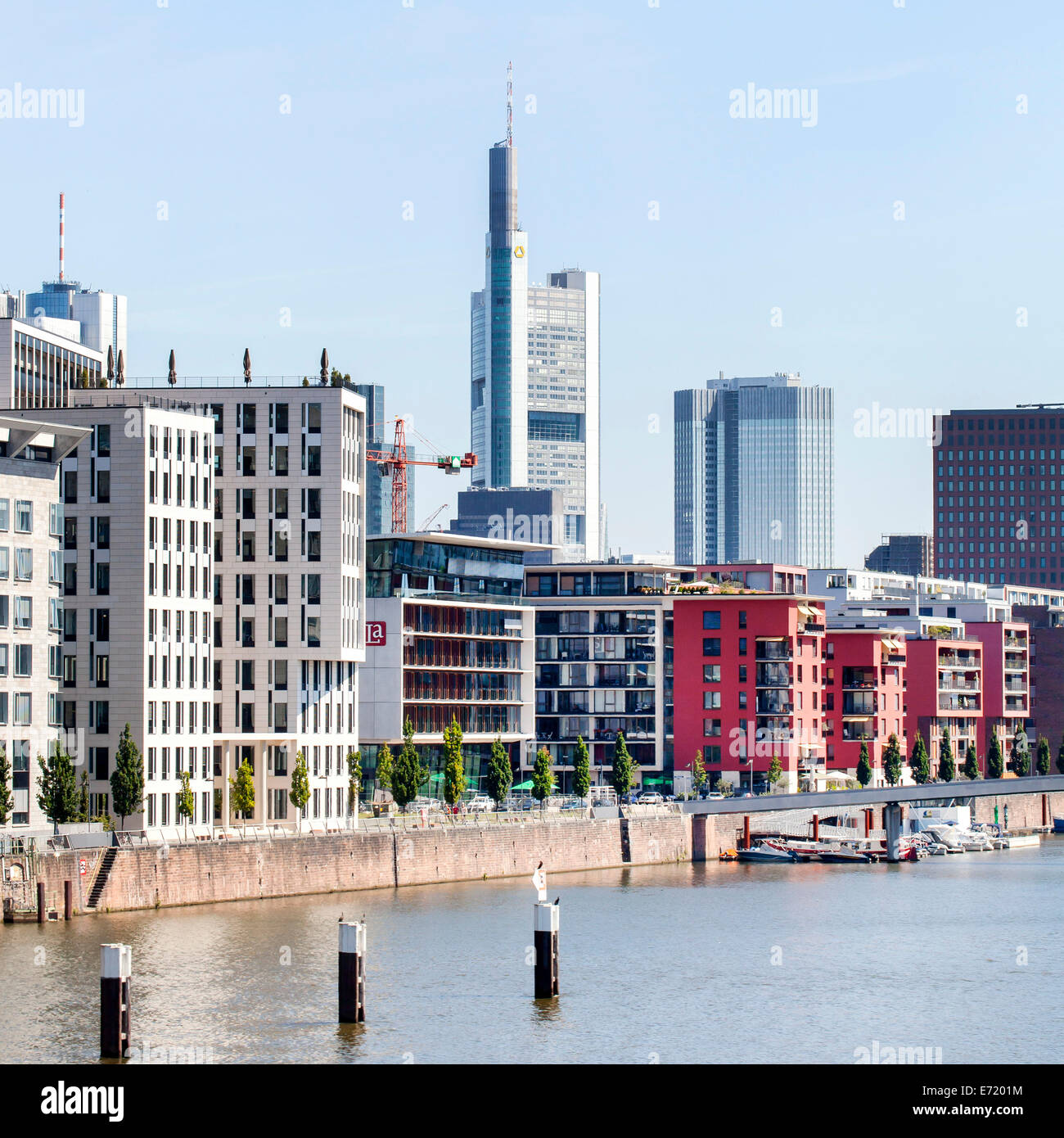Residential building with luxury apartments in Frankfurt's West Harbour, Commerzbank tower at the back, Frankfurt - Stock Image