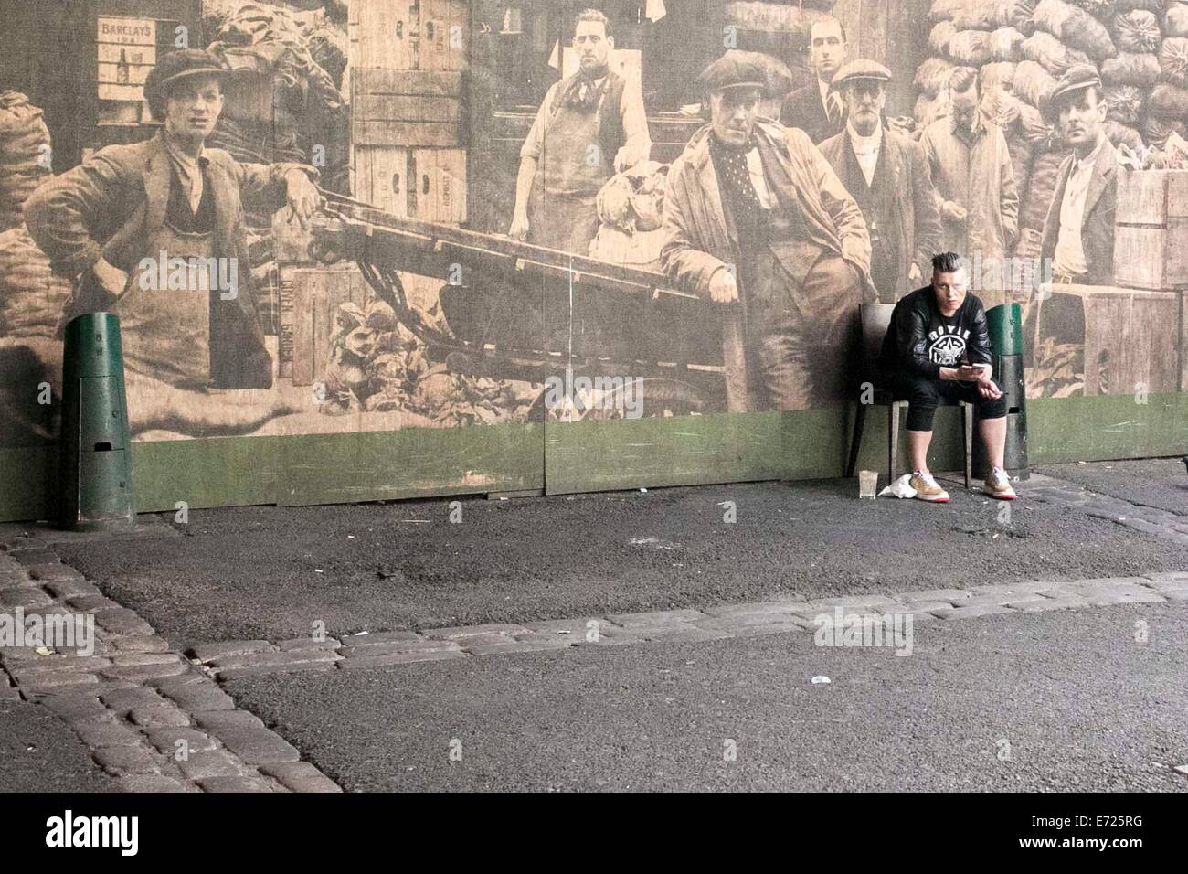 Borough Market , London. A young man sits in front a large historical photo of the market. - Stock Image