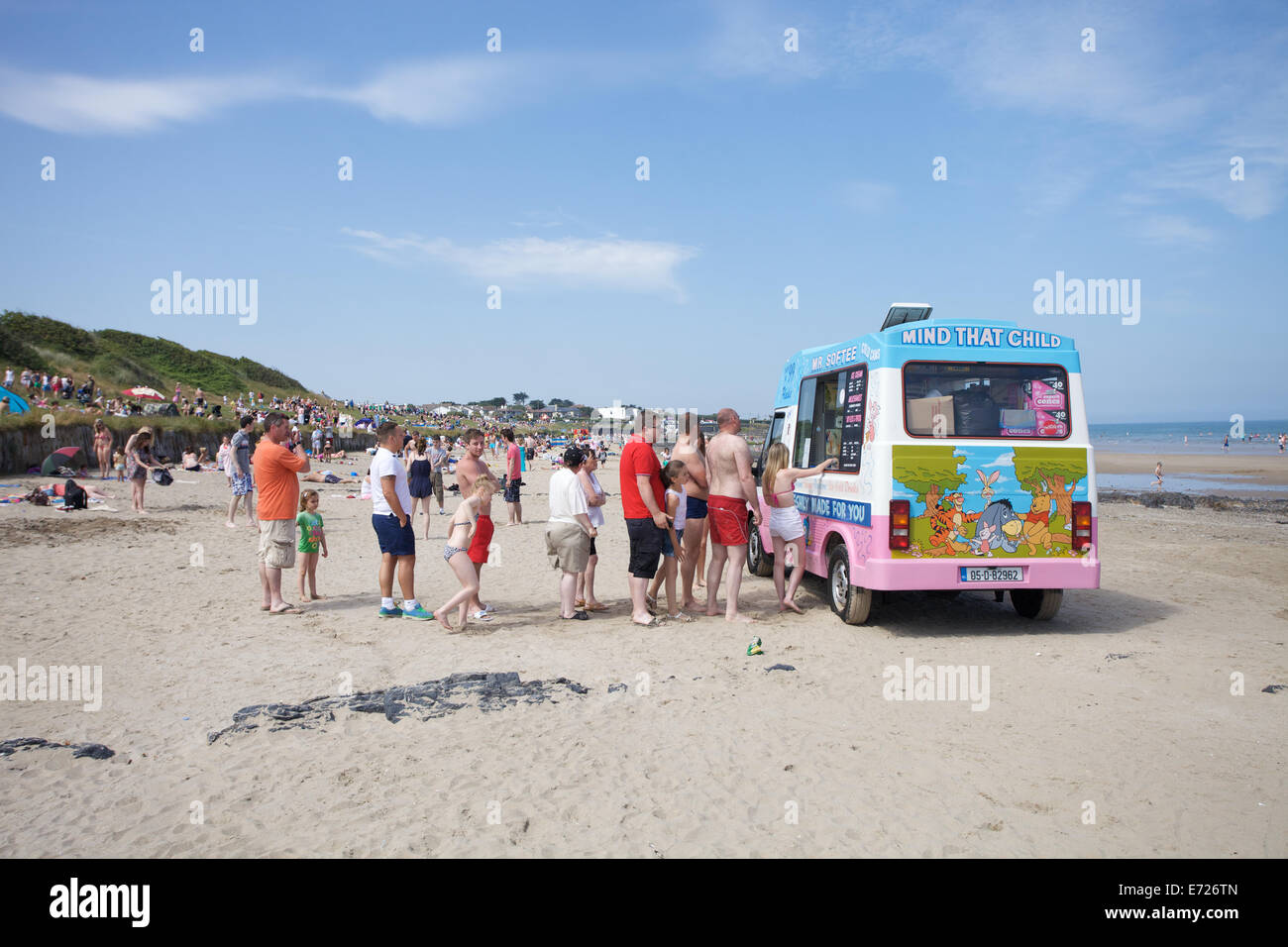 People queuing for ice cream from an ice cream van on the beach at Portmarnock in Dublin, Ireland - Stock Image