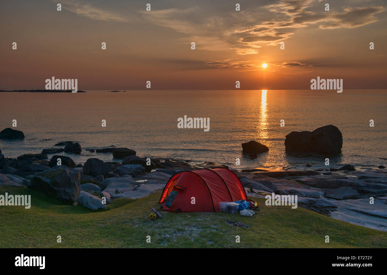 Enjoying the midnight sun on beautiful Uttakleiv Beach in the Lofoten Islands, Norway - Stock Image