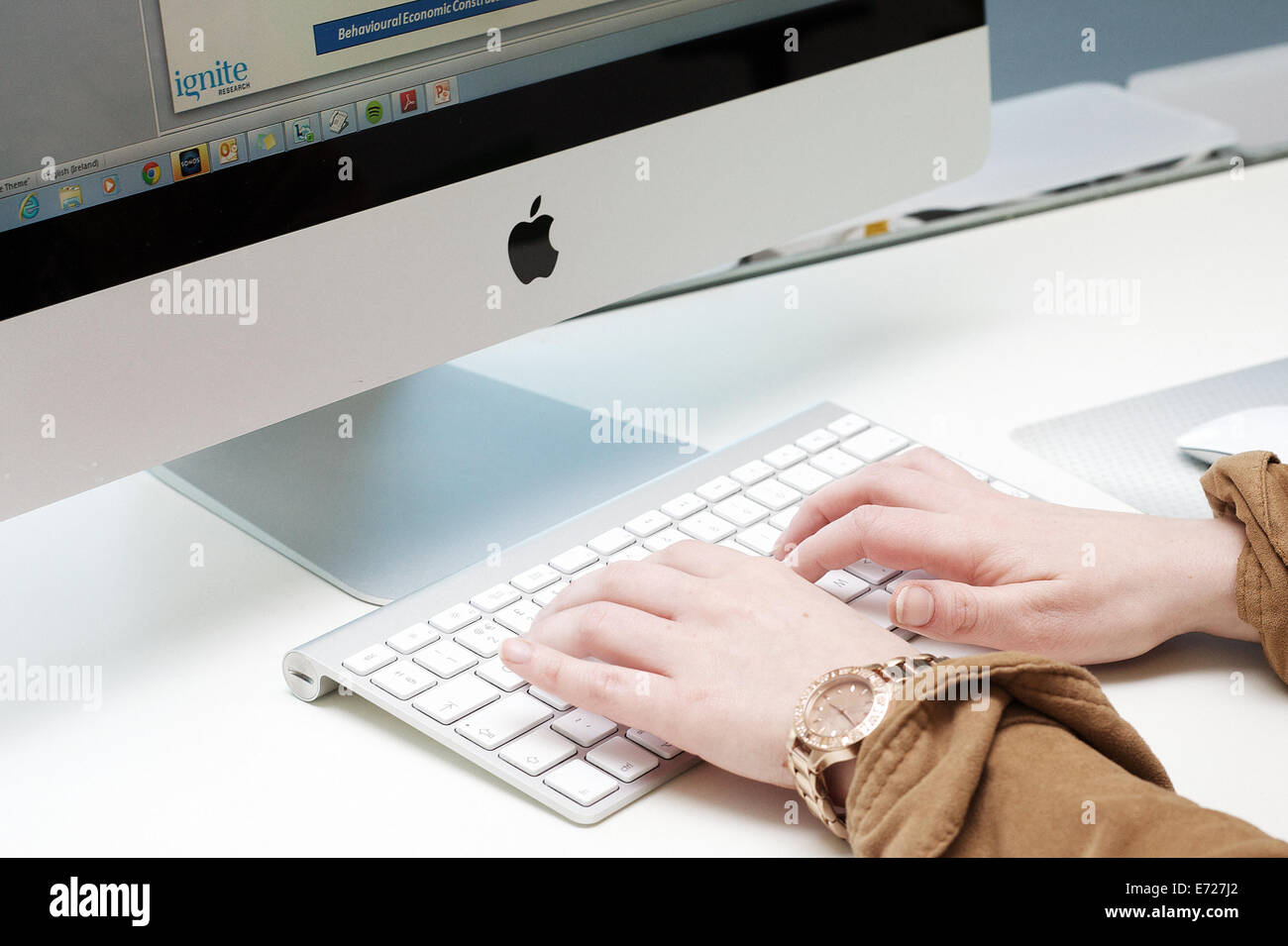 Female hands typing on the keyboard of an Apple Imac