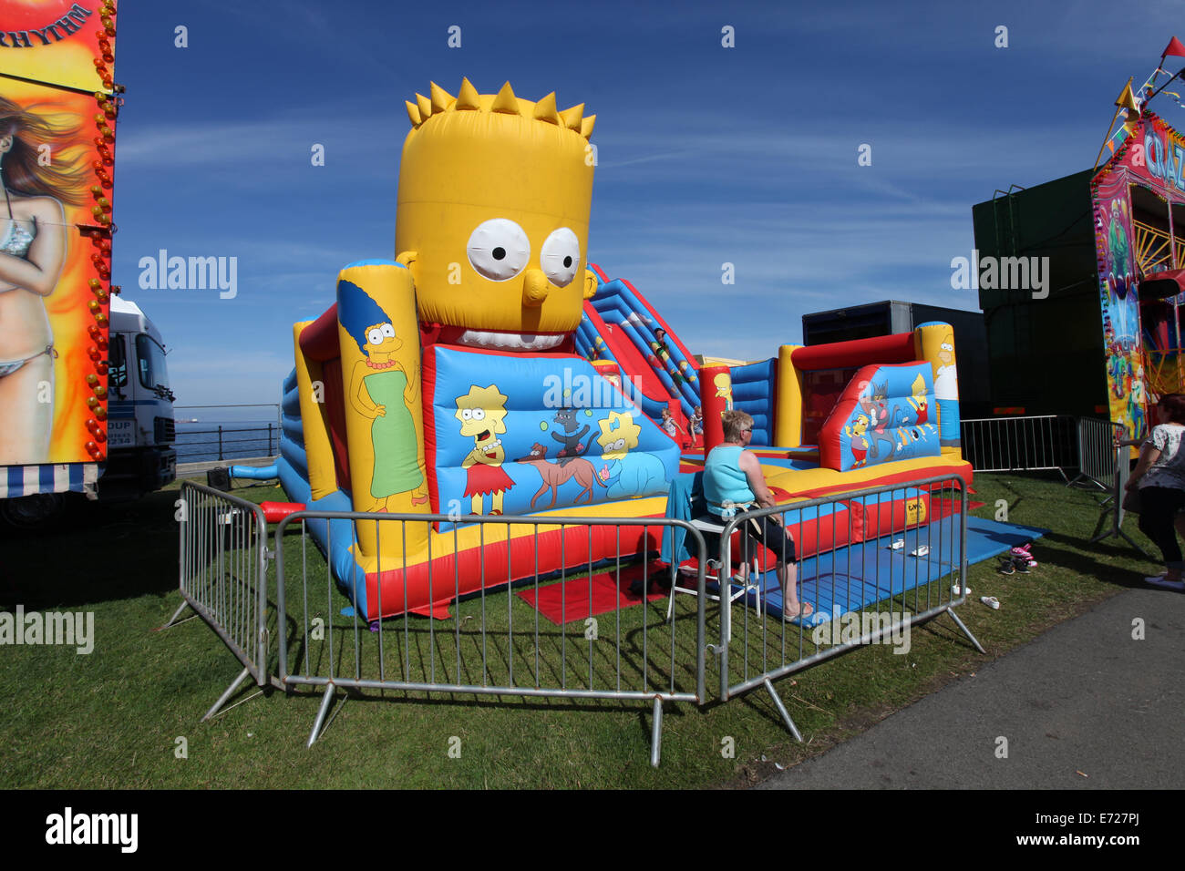 A bart simpson bouncy castle at a funfair - Stock Image