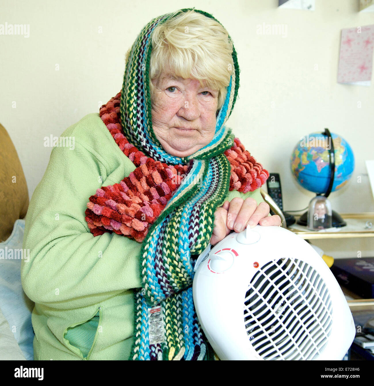 Old lady trying to keep warm in a cold winter - Stock Image