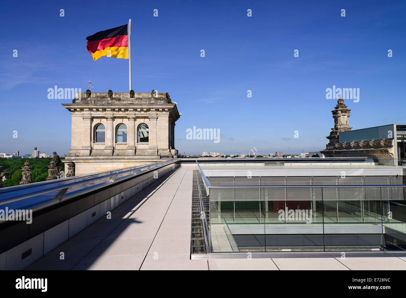 Germany, Berlin, German flag fluttering on a corner tower of the Reichstag building as seen from the rooftop terrace. - Stock Image