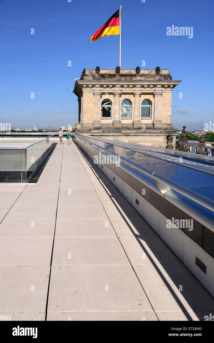 Germany, Berlin, German flag fluttering on a corner tower of the Reichstag building as seen from the rooftop terrace - Stock Image