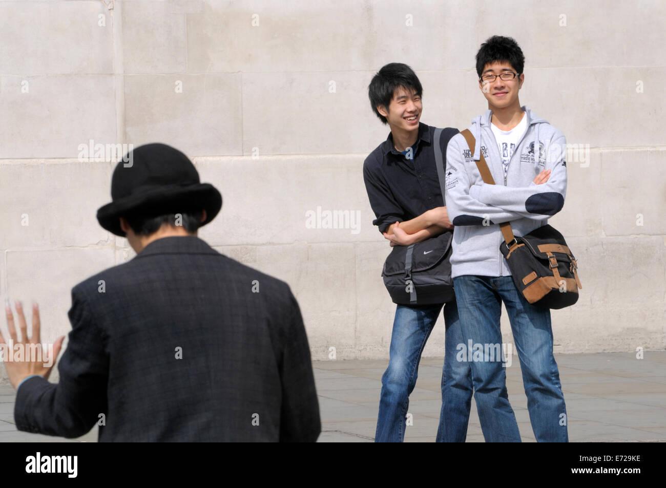 London, England, UK. Japanese tourists watching a mime artist in Trafalgar Square - Stock Image