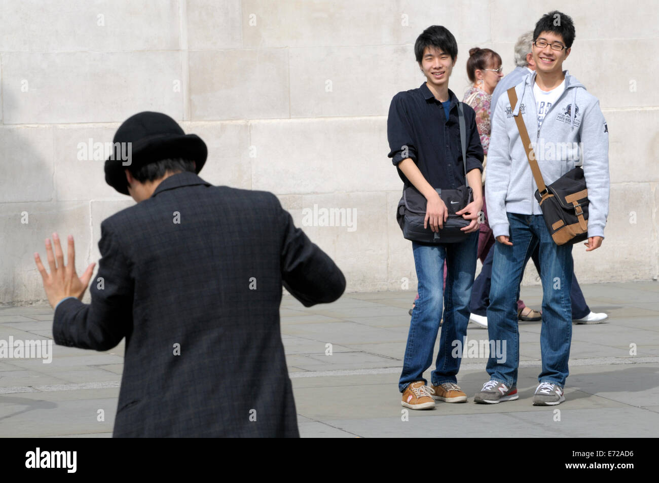 London, England, UK. Tourists watching a mime artist in Trafalgar Square Stock Photo