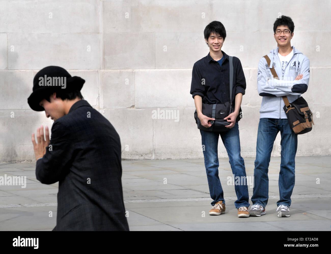 London, England, UK. Tourists watching a mime artist in Trafalgar Square - Stock Image