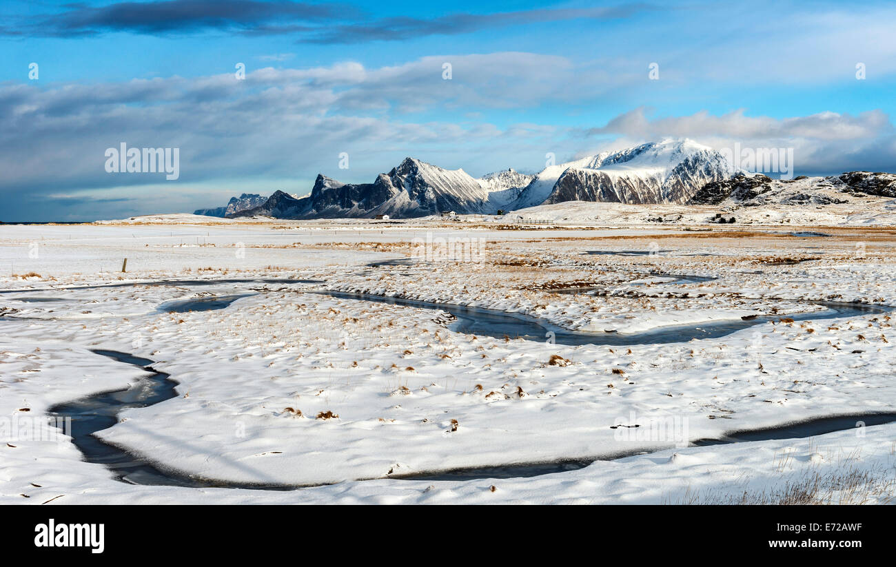 A frozen stream meandering through the snow at Fredvang on the Lofoten islands - Stock Image