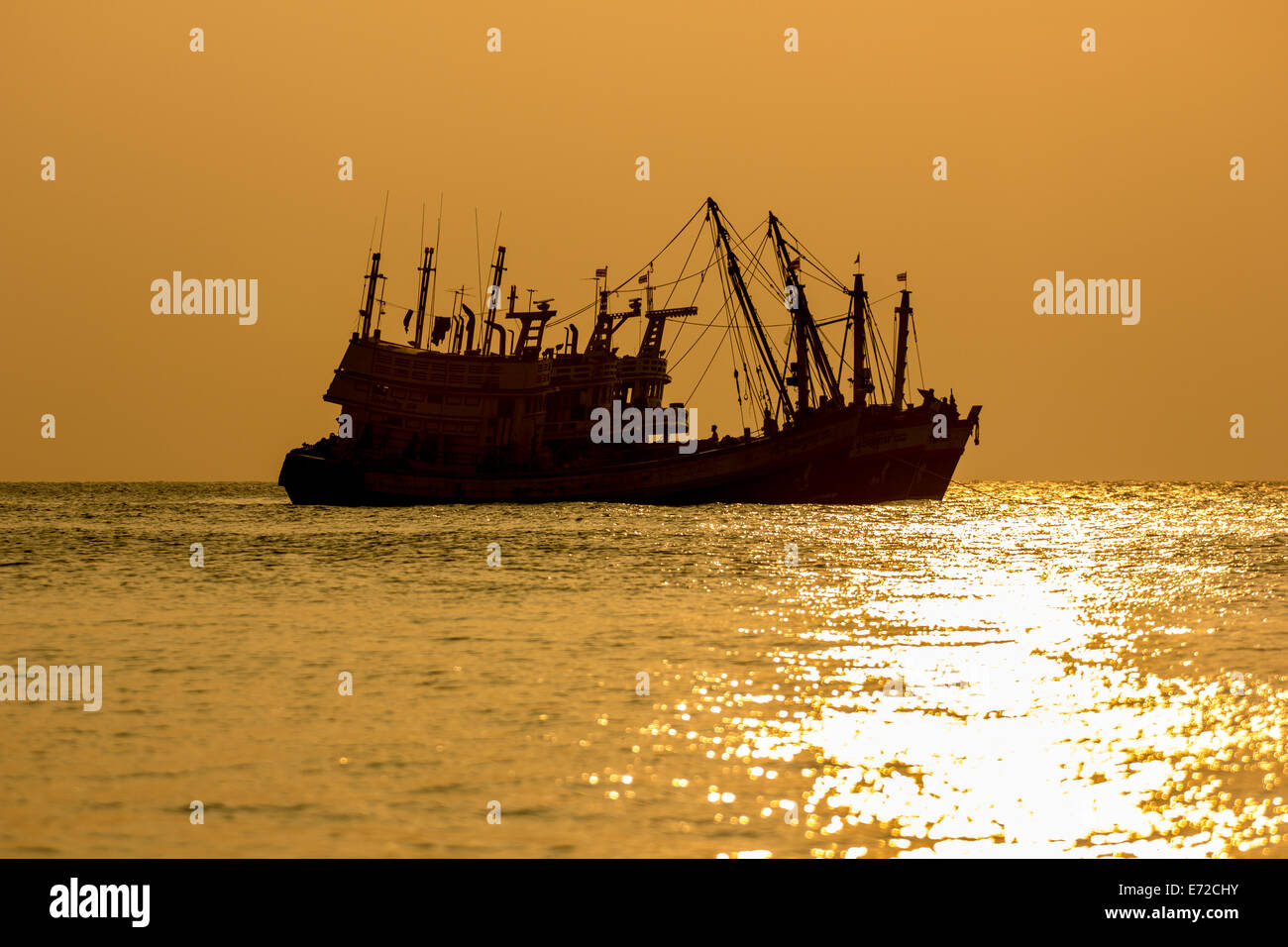 the sillhouette fishing boat on sunset - Stock Image
