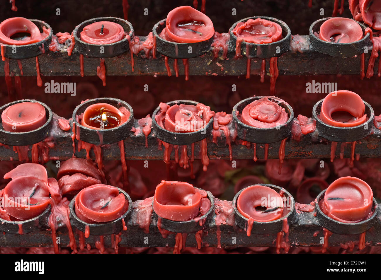 Lit and unlit red little candle offerings of people for their loved ones and prayer requests - Stock Image