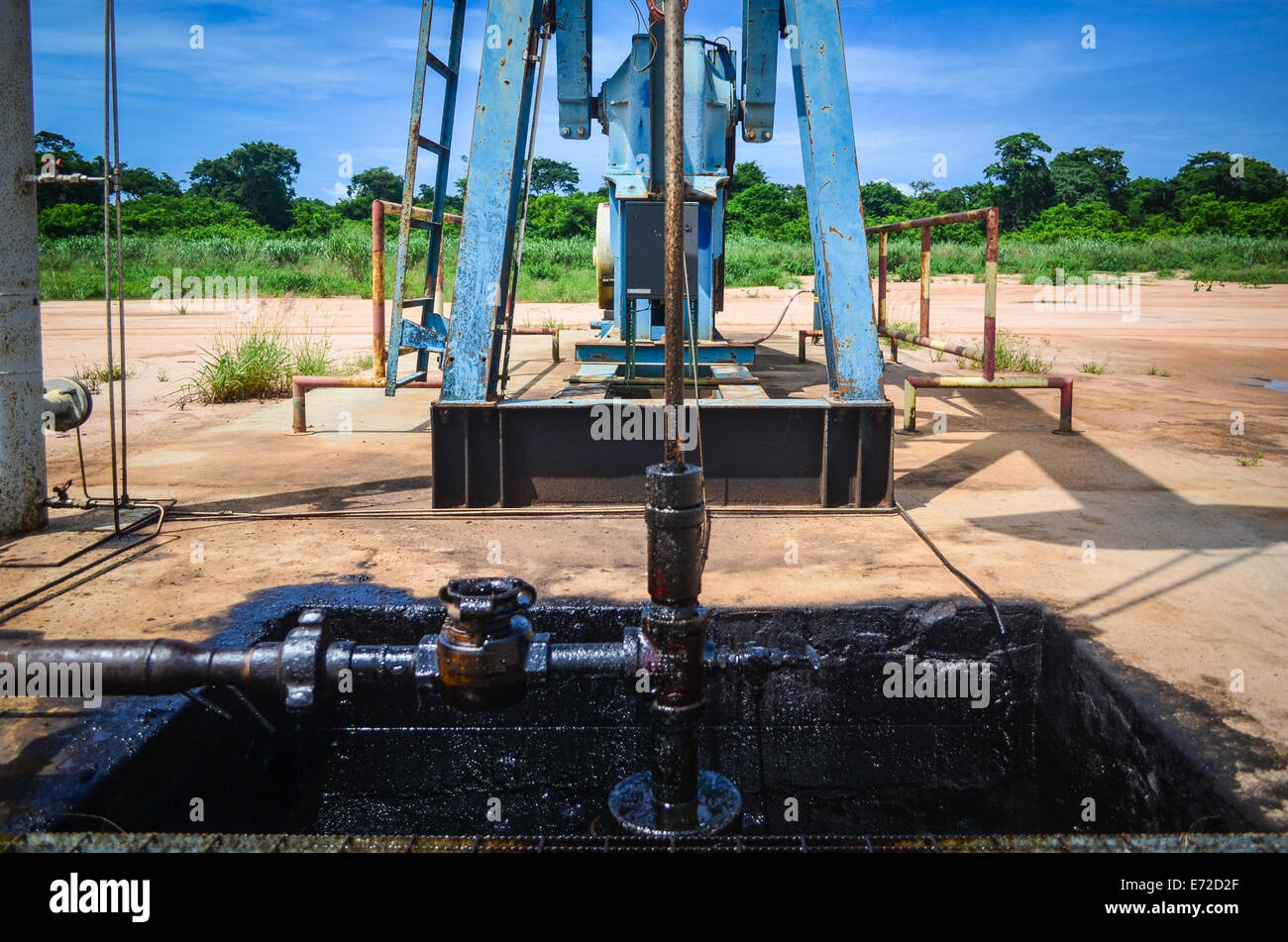 Onshore oil well (pumpjack) in Angola (Soyo province), close-up on the pump and petrol spill - Stock Image