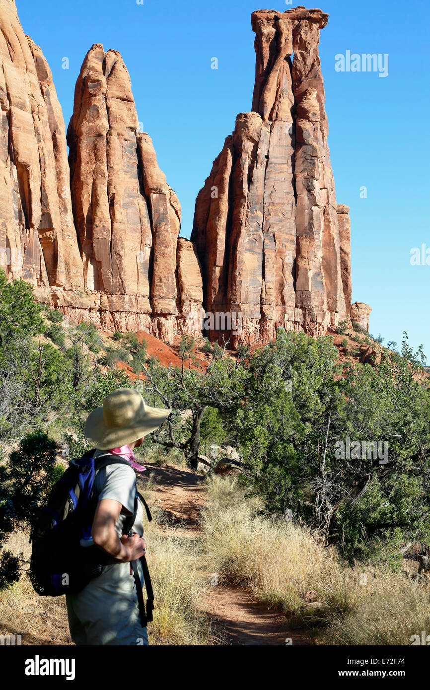 Female hiker below Kissing Couple sandstone monument, Canyon Monuments Trail, Colorado National Monument, Grand Junction USA Stock Photo