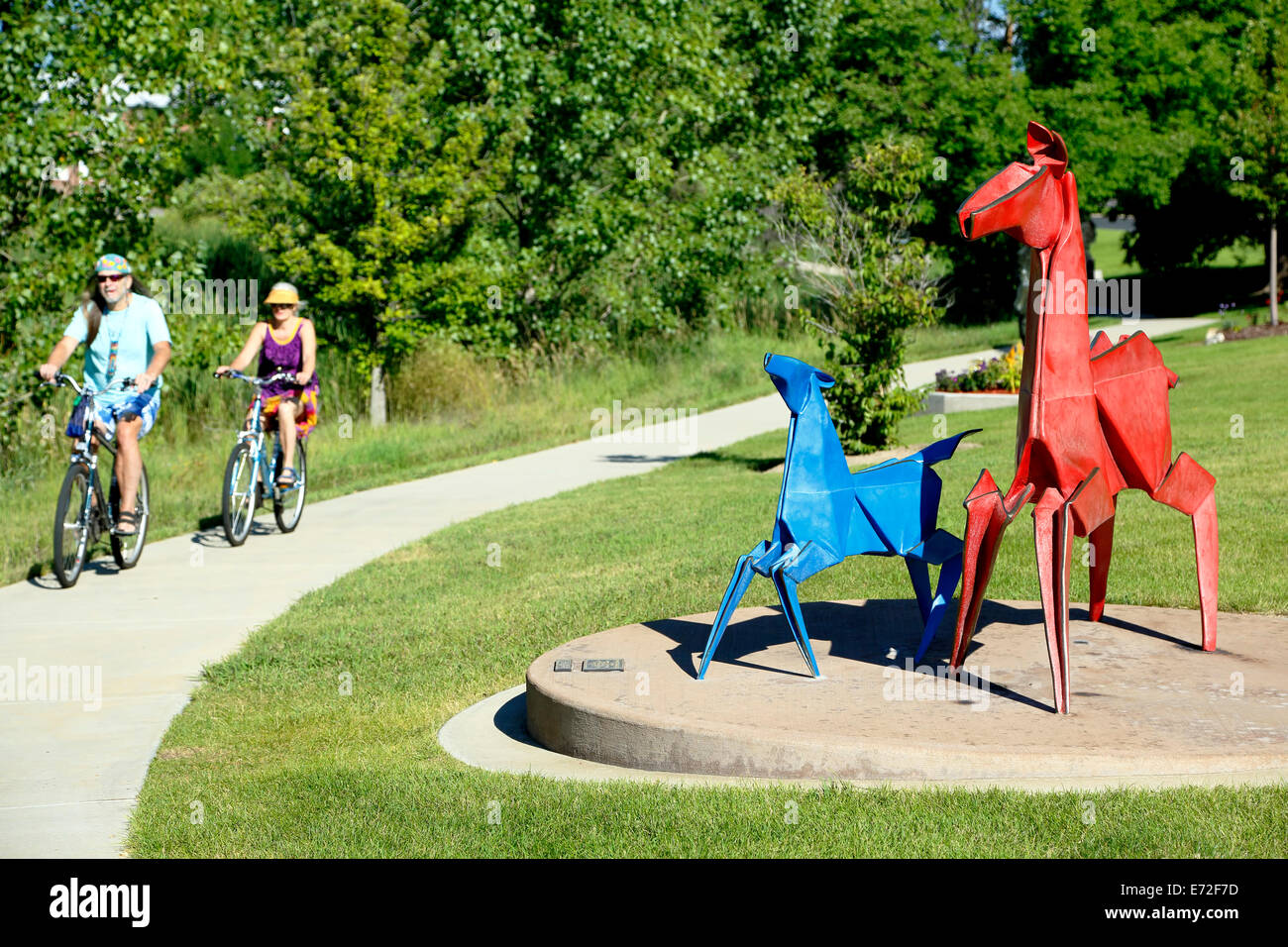 'Red and Blue Pony' sculpture, by Kevin Box, and bicyclists on trail, Benson Sculpture Garden, Loveland, - Stock Image
