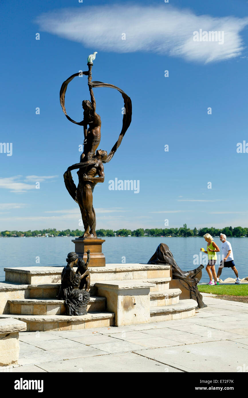 'Generations' sculpture, joggers and Lake Loveland, Loveland, Colorado USA - Stock Image
