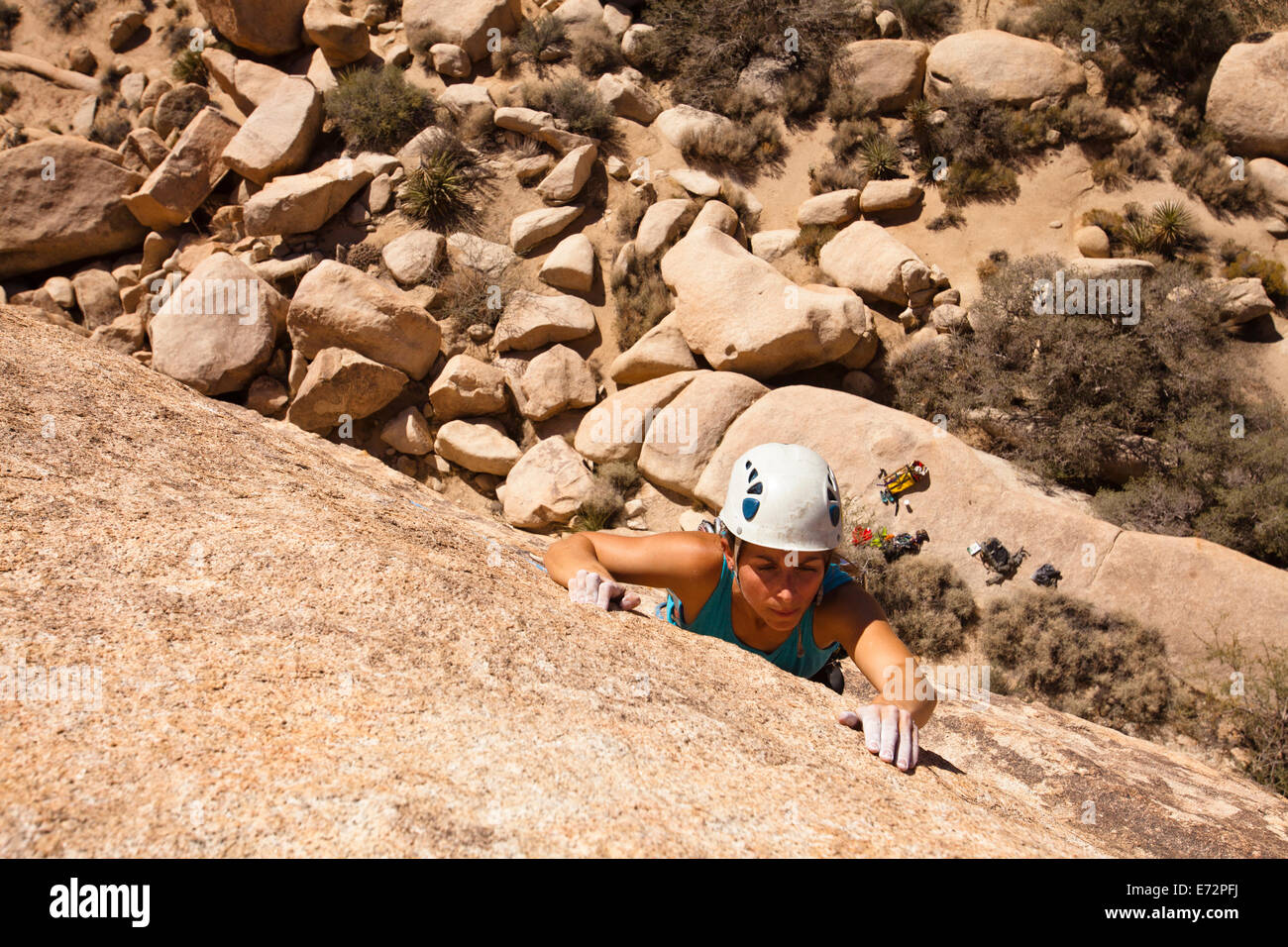 A female climber searches for handholds while finishing the traverse on Sidewinder (5.10b) in Joshua Tree National - Stock Image