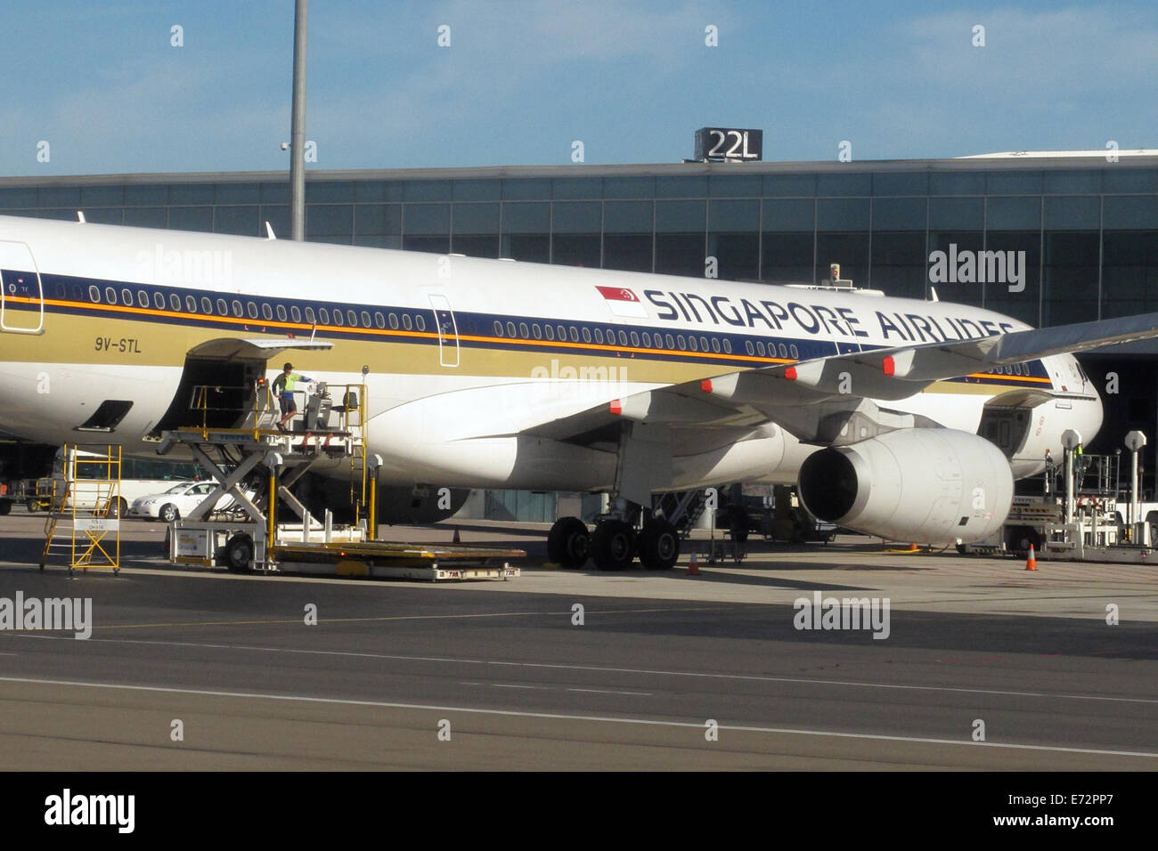 Singapore Airlines plane being loaded with luggage on the tarmac of Adelaide Airport in Australia. - Stock Image