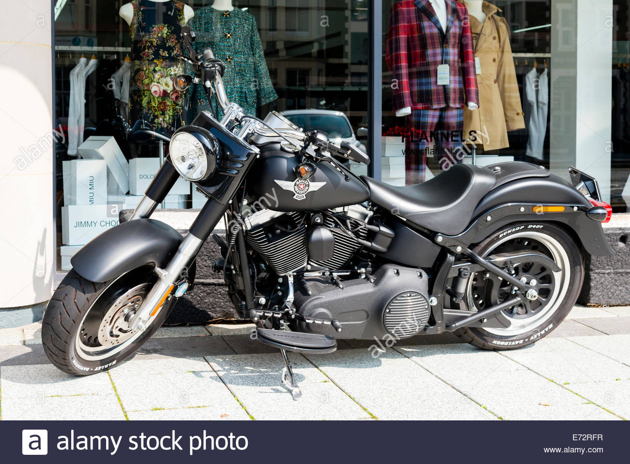 Harley Davidson motorcycle parked outside a shop, UK. - Stock Image