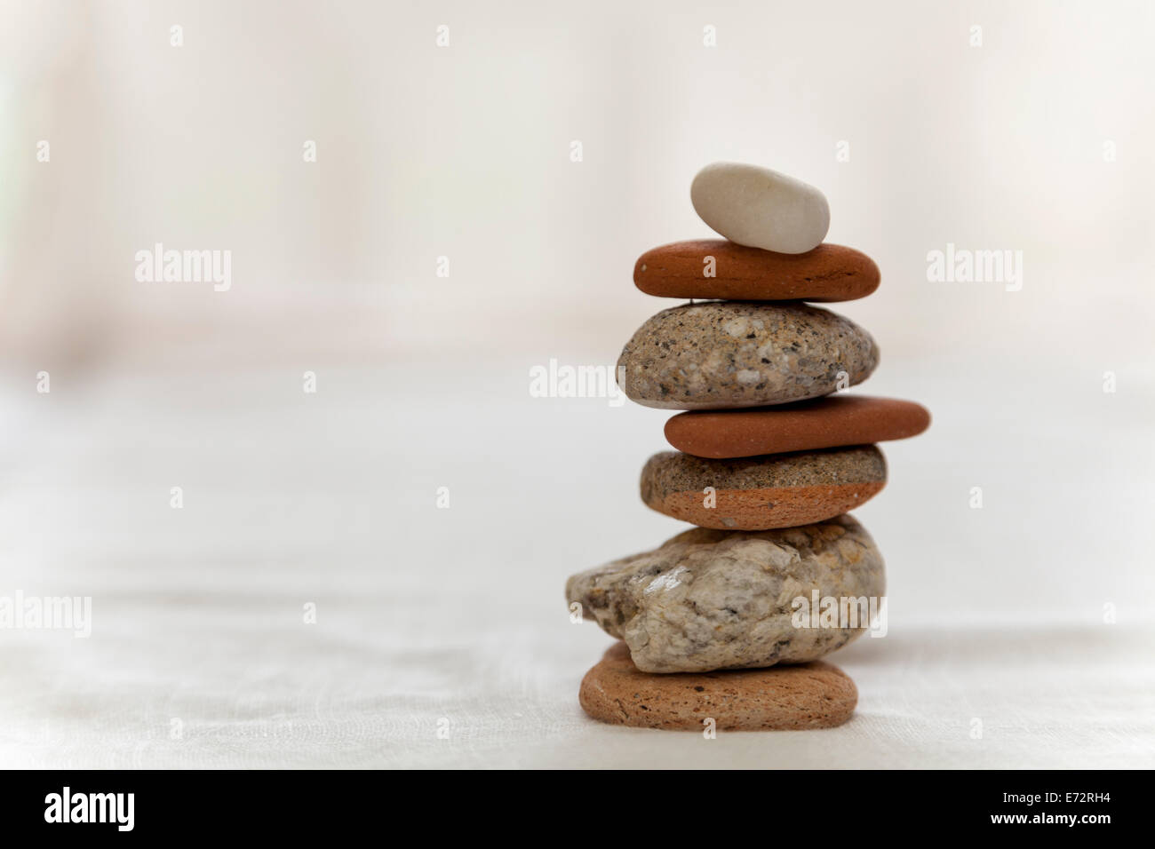 Still life; stone-stacking, pebbles stacked and sitting on a white table top with white background. Zen like practice - Stock Image