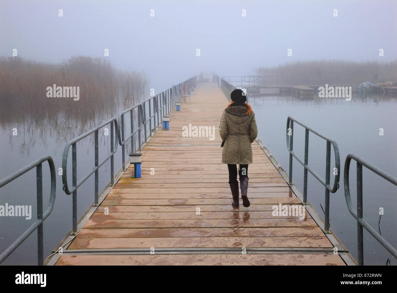 Lonely woman walking  the floating pedestrians' bridge of Agios Achilleios islet, Mikri Prespa lake, Florina, - Stock Image