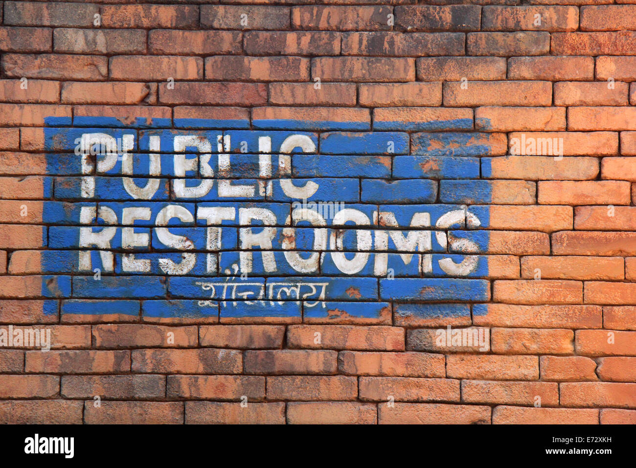 Public restrooms sign with Hindi writing below. - Stock Image