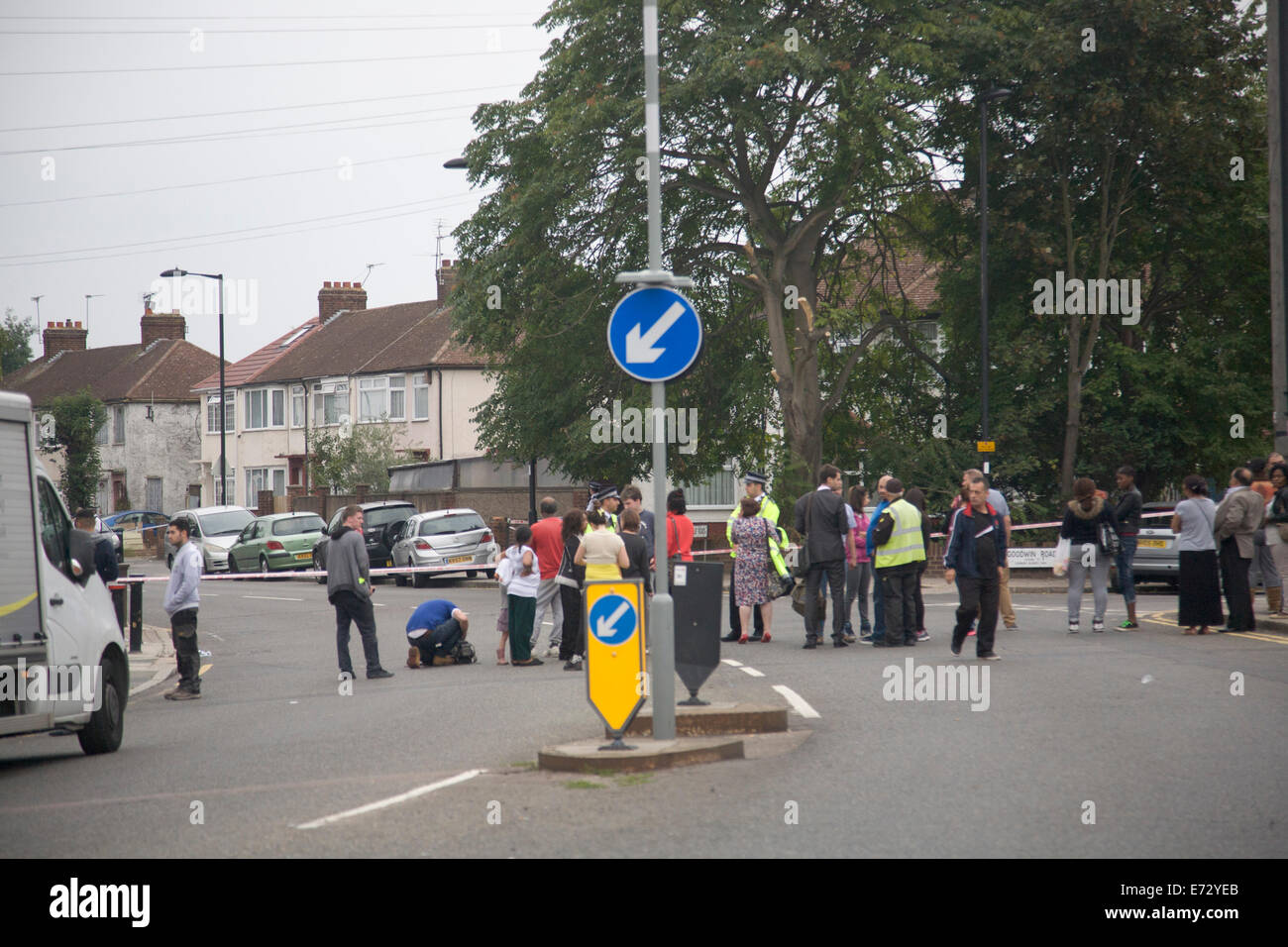 Edmonton London,UK. 4th September  2014. Resident onlookers watch behind police tapes near the crime scene after - Stock Image