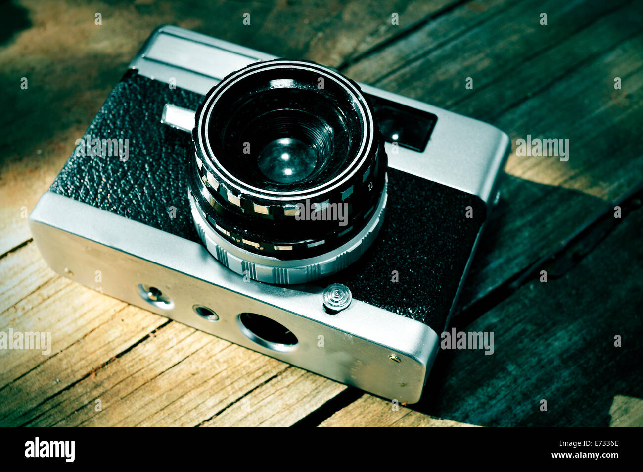 an old camera on a rustic wooden surface - Stock Image