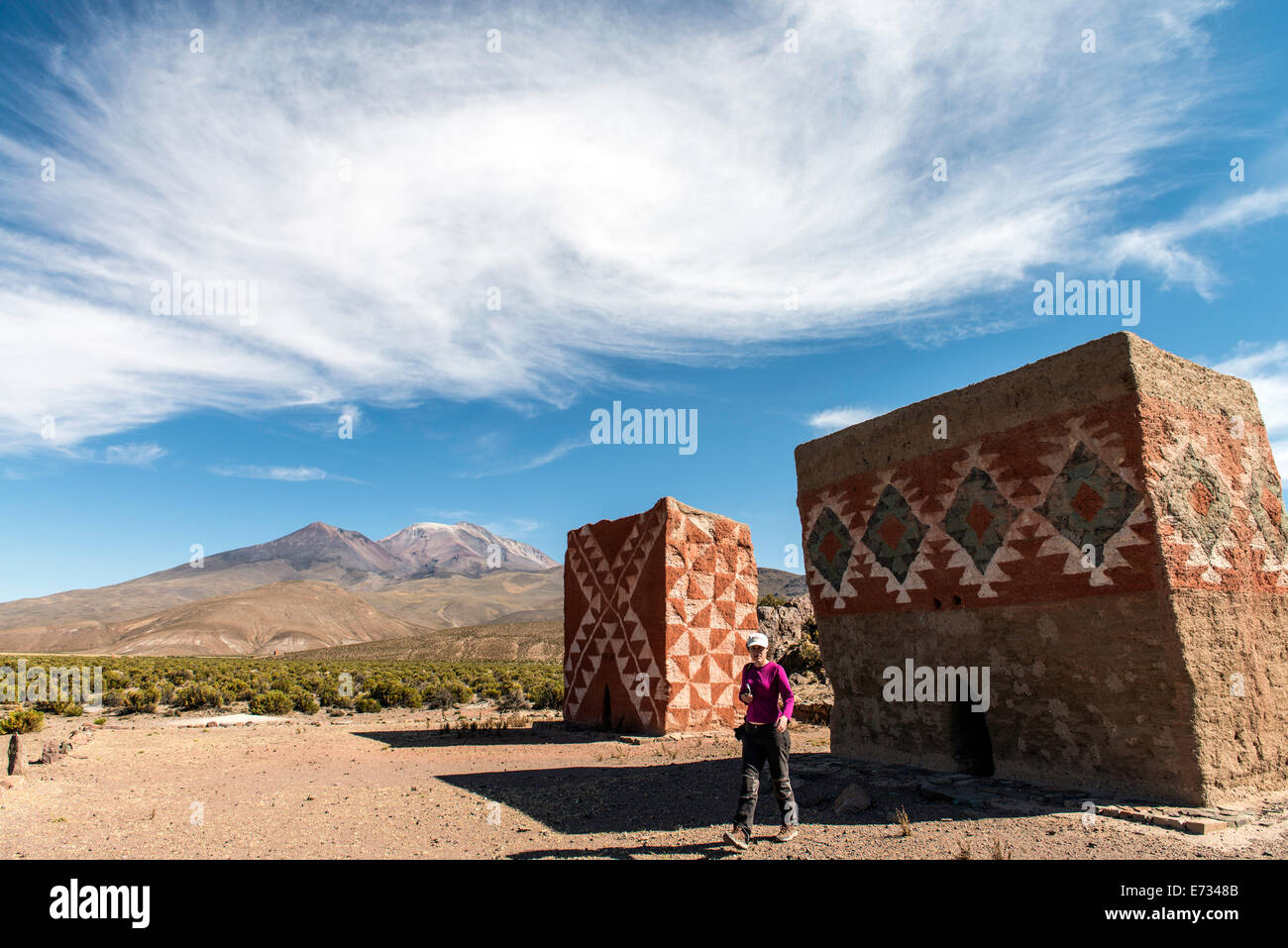 Woman walking by Coloured chullpas or burial towers (Pre-colonial tombs) in Rio Lauca valley, Bolivia, South America - Stock Image