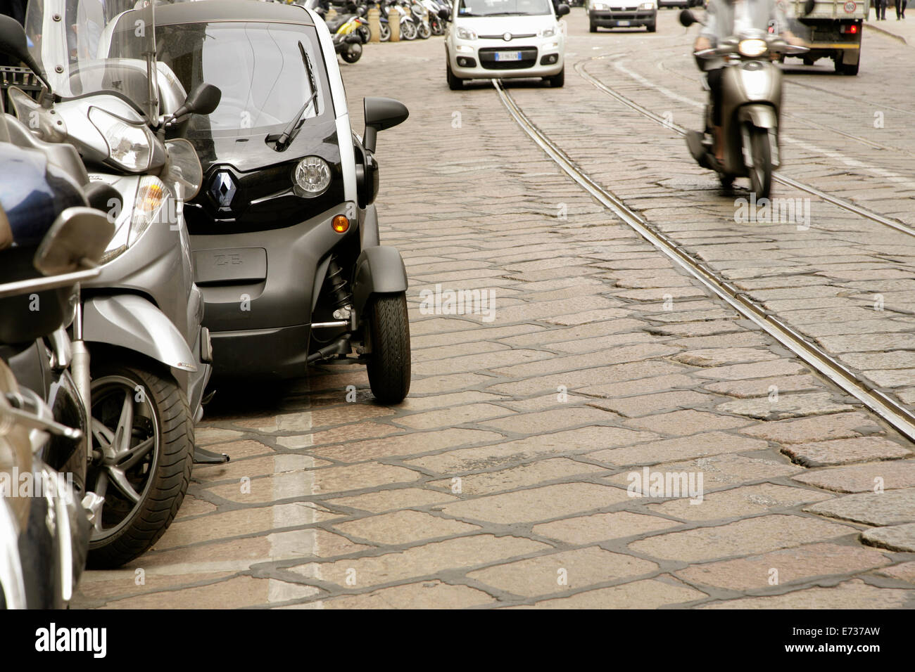 Motorscooter passing Renault Twizy electric microcar near La Scala, Milan, Italy. Stock Photo