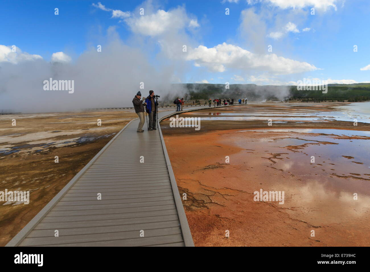 Tourist taking a photograph of Grand Prismatic Spring, Midway Geyser Basin, Yellowstone National Park, UNESCO Site, Stock Photo