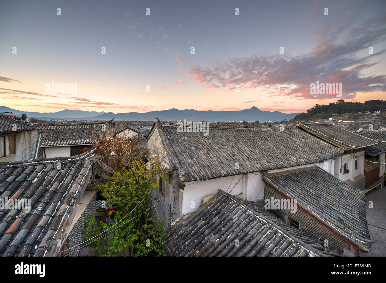 The sun is about to rise over the roofs and mountains of Lijiang Old Town, UNESCO Site, Lijiang, Yunnan, China, - Stock Image